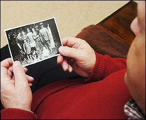 Survivor looks at picture of his family