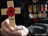A war veteran holds a holds a remembrance cross