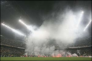 Smoke rises above the San Siro through flares