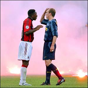 AC Milan's Clarence Seedorf and Inter Milan's Estaban Cambiasso chat as smoke billows at the San Siro