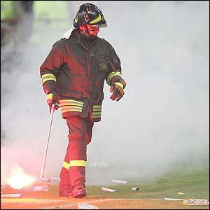 A Fireman removes hundreds of object from the San Siro pitch