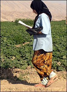Young girl reads schoolwork while walking by fields of crops