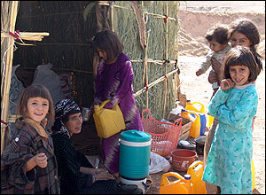 Young girls standing by their home in Dareh Shahr