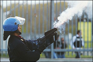A policeman shoots tear gas towards Juventus fans