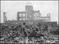 A man stands in a sea of rubble in front of a building that once was a cinema in Hiroshima in 1945