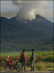 Indonesians chat as volcanic clouds spew from the crater of Mount Talang
