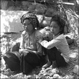 A Vietnamese mother and daughter come out of their shelter