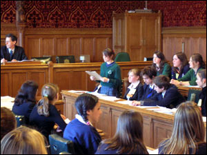 The students arguing against lowering the voting age sit on the left of the speaker. This is where the opposition party would sit in the House of Commons.