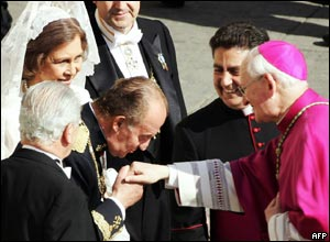 Spain's King Carlos kisses the hand of a US cardinal, while Queen Sofia looks on.