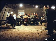 Military leaders seated round table in tent at night