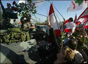 A Lebanese woman throws flowers at Lebanese soldiers as