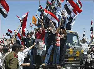 Syrians wave portraits of their president and national flags as they welcome home their troops from Lebanon