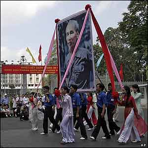 Youths parade holding large poster of Ho Chi Minh