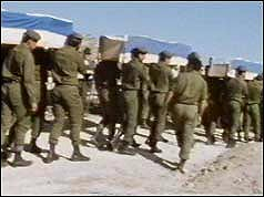 Soldiers bearing coffins on shoulders
