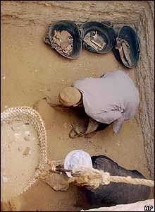 Egyptian labourers clear sand from the pit where the mummy was found