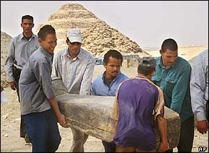 Workers carry decorated mummy with Step Pyramid in the background