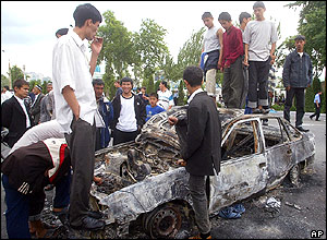People stand on burned-out car, Andijan
