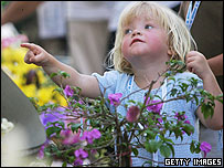 A young girl points at flowers at a tsunami memorial service