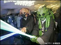 Fans queuing for the midnight use their lightsabres