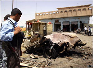 Iraqi police officer looks at debris from car bomb