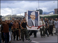 Young Nepalese men hold up image of the murdered king