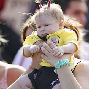 A baby girl watches the Liverpool parade