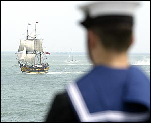 A sailor aboard HMS Invincible watching the tall ship Grand Turk