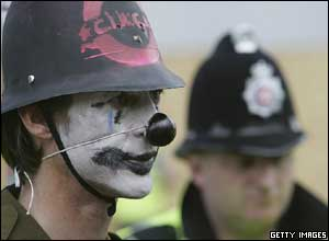 A protester in fancy dress confronts police in the financial district of Edinburgh