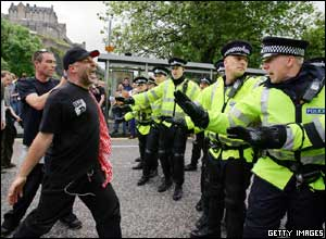 A protester faces Police officers as he participates in the ' Carnival for Full Enjoyment