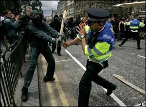 A masked protester clashes with a police officer during the 'carnival for full enjoyment