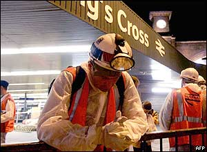 A construction worker bows his head in prayer at Kings Cross station in London