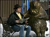 A man sitting next to a metal bear