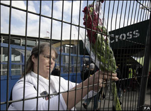 Tina Debenham attaches a floral tribute to the railing outside Kings Cross