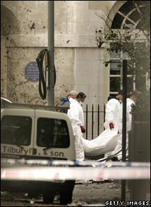 Police forensic officers remove a body from the scene of a bus bombing