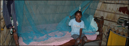 Angeline using a mosquito bed net (Picture: UNICEF UK/2004/Dianne Male)