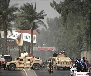 US and Iraqi military and police vehicles arrive at the scene of a suicide attack on a Baghdad army recruitment centre