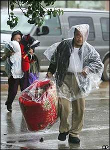 A Pensacola father and his daughter carry blankets and pillows into a shelter