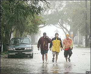 Key West residents walk through a flooded street