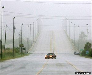 A lone car drives through the rains from Hurricane Dennis in Mobile, Alabama