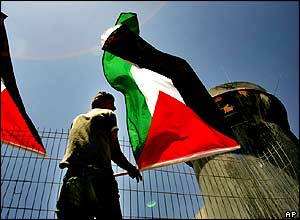 A Palestinian youth waves the Palestinian flag next to an Israeli army watchtower during a demonstration against the construction of Israel's separation barrier at the Kalandia checkpoint.