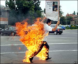 Iulian Grosu runs after setting himself on fire in Bucharest, Romania, in an apparent desperate bid to get custody of his son who is living in Spain.
