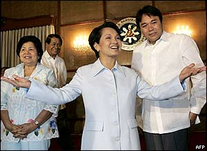 Philippine President Gloria Arroyo (C) gestures while meeting with local government officials before a luncheon at the Malacanang presidential palace in Manila, 13 July 2005.
