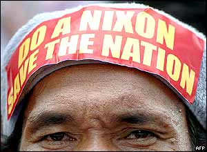 A protester with a sticker reading 'Do a Nixon - Save the Nation