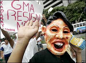 A protester wearing a mask of Philippine President Gloria Macapagal Arroyo joins thousands others during a rally calling for her resignation in the district of Makati, south of Manila on July 13, 2005