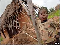 一男孩站在被毀的家園前