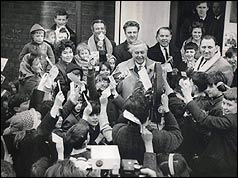 Harold Wilson surrounded by children waving leaflets