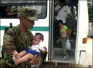A Mexican soldier carries a baby into a shelter