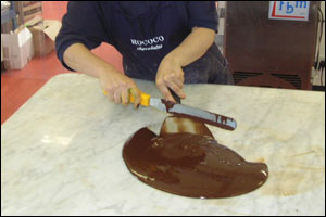 This involves swishing it about on a big marble slab. This process makes sure the choccie is crisp and makes a snapping sound when we break it