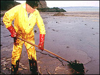 Man cleans up an oil spillage on a beach
