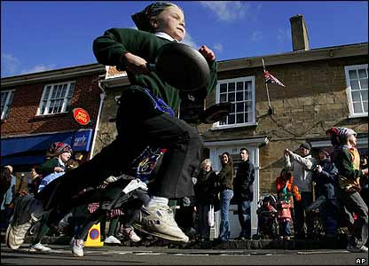 Here a pupil from an Olney school takes part in the race, where contestants run as fast as they can to the church, while carrying a pancake in their frying pan